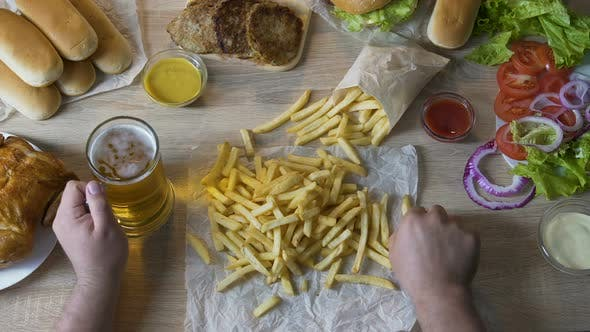 Thumbnail for Man Pouring French Fries in Sauce and Drinking Beer Unhealthy Eating Calories