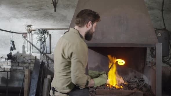 Thumbnail for Blacksmith Melting Metal in Workshop