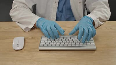 A Man in Blue Protective Gloves and a White Coat Uses a Computer Keyboard. Sanitation Process and