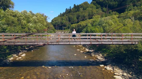 Thumbnail for Aerial View From Old Wooden Suspension Bridge Over a Mountain River. Girl Standing on a Wooden