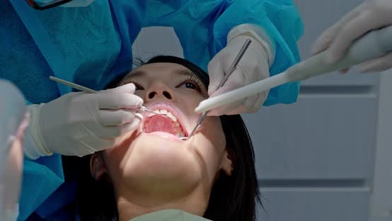 Thumbnail for Dentist treating teeth to woman patient in clinic