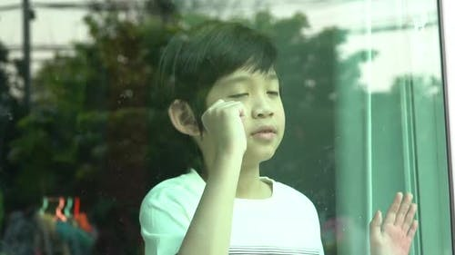 Unhappy Asian Child Behind A Window
