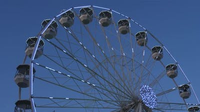 Ferris wheel in action againts a blue sky.