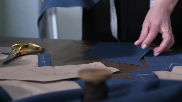 Thumbnail for Dressmaker's Hands Laying Out Cut Pattern on Table