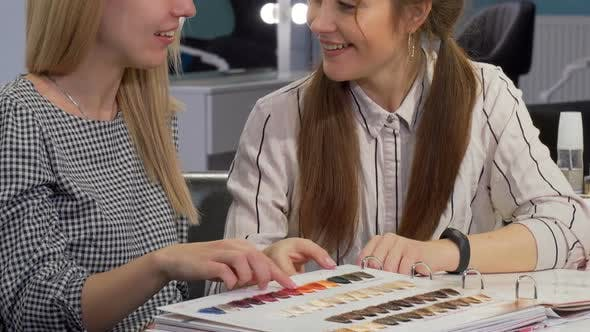 Thumbnail for Two Female Friends Examining Hair Color Dye Chart at Beauty Salon