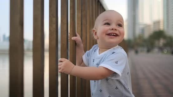 Thumbnail for Laughing Boy at the Age of 1 Year Dancing Holding the Railing and Learning To Walk Making the First