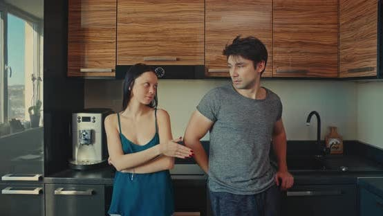 Cover Image for Young Couple in an Argument in a Kitchen. Make Peace Start Kissing.