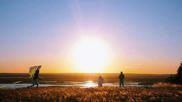 Thumbnail for Young Family Standing on the Hill on an Early Sunset - a Little Girl Playing with the Kite and