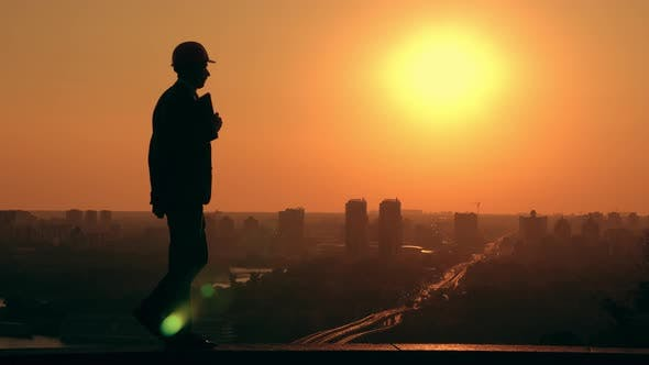 Thumbnail for Male Architect in a Hard Hat at Work Cityscape at Sunrise