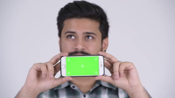 Thumbnail for Young Happy Bearded Indian Man Thinking While Showing Phone
