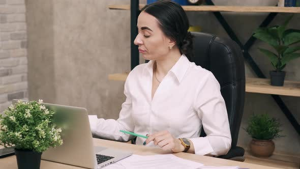 Tired Woman Working in Office and Drinking Coffee