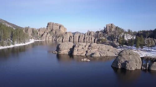 Aerial Flyover of Lake or Pond Reservoir Impoundment in Black Hills Western North America Forest