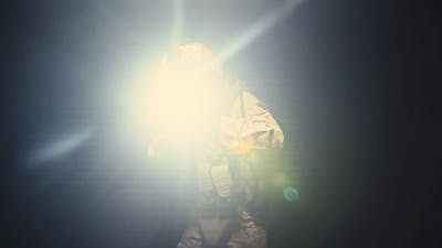 Soldier in Camouflage with a Gun is Moved in the Darkness