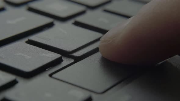 The Finger Presses the Enter Button on the Keyboard