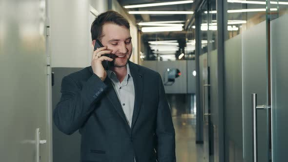 Portrait of a Young Smiling Businessman Talking on a Cell Phone