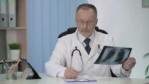 General Practitioner Examining X-Ray, Filling Medical Form for Hospitalization