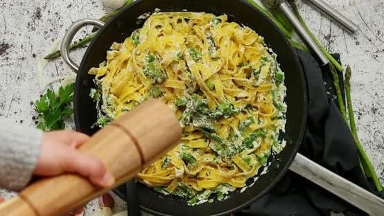 Frau Hinzufügen von frischem Pfeffer zu hausgemachten Tagliatelle Pasta mit Ricotta-Käse-Sauce und Spargel