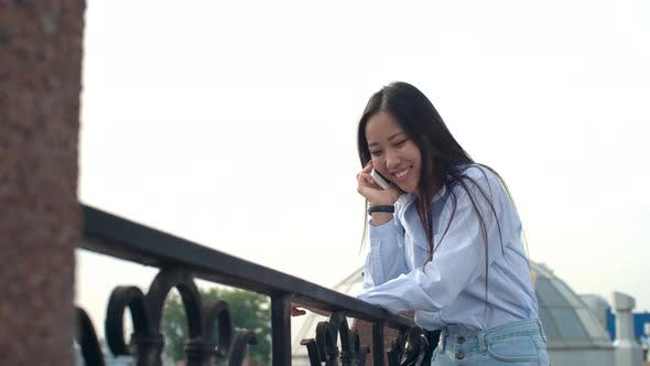 Cover Image for Happy Asian Lady Chatting on Phone at Summer Day Outdoors