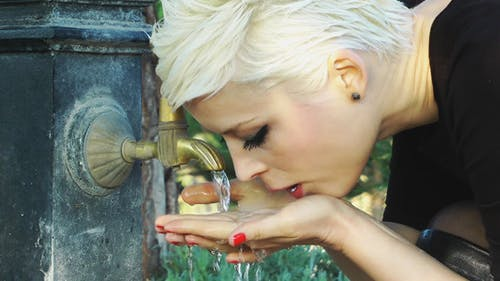 Lady Drink Water From An Old Fountain