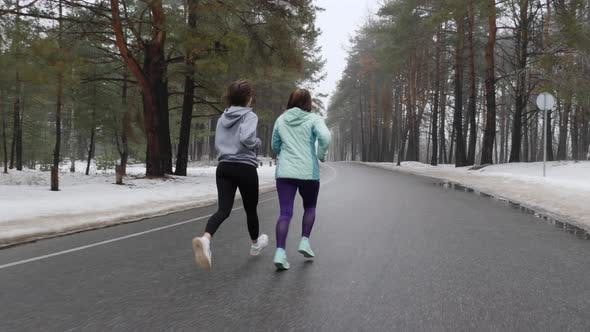 Thumbnail for Senior and Young Women Running in The Snowy Park in Winter Talking and Smiling