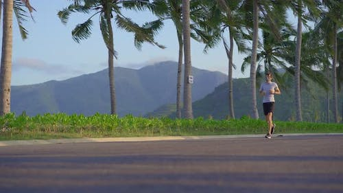 A Man Wearing a Face Mask is Running on a Street in a Tropical Surrounding