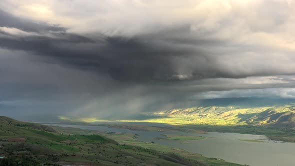 Cover Image for Storm Clouds and Rain Approaching to Lake Geography Surrounded by Hilly Meadows