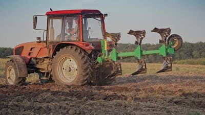 Tractor plowing land. View of red tractor in the agricultural field