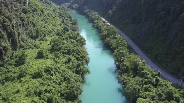Thumbnail for Aerial Motion Above Jungle River and Highway in Canyon
