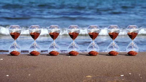 Row of Sandglass Clocks with Golden Grains Stands on Beach