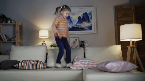 Thumbnail for Little Girl Child Jumps On Sofa Home Having Fun