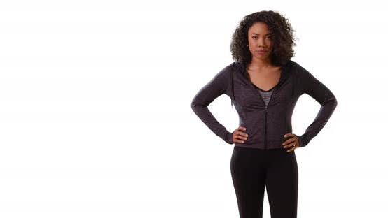Fit black female jogger posing with hands on hips on white background
