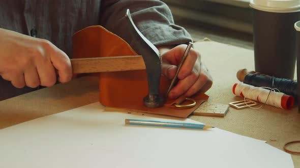With a Core and Hammer, the Tanner Punches Holes for Sewing an Exclusive Bag Made of Genuine Leather