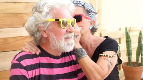 Senior old caucasian couple with alternative look and cheerful lifestyle engage and have fun