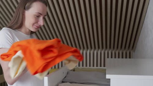 Woman Put Clothes in Chest of Drawers