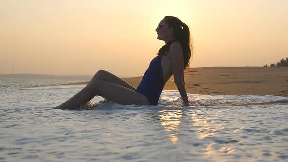 Thumbnail for Ocean Waves Washing Over Tanned Female Body. Cute Girl Lying on the Beach in the Waves at Sunset