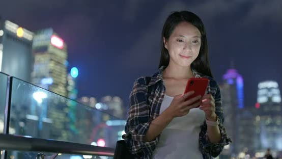 Thumbnail for Woman use of mobile phone in city of Hong Kong at night