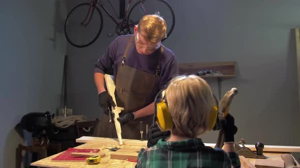Thumbnail for Man Works with Wood and Boy Looks at Him
