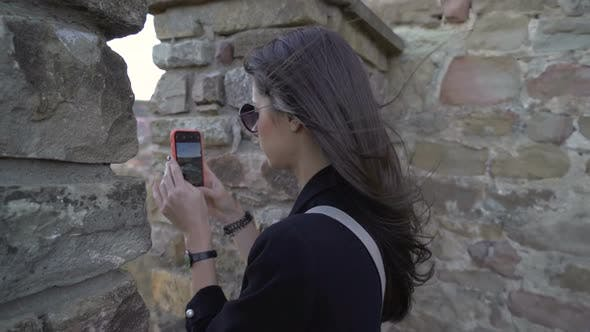 Thumbnail for Tourist Girl Watching Trough Medieval Fortress Wall and Taking Pictures of the Panoramic View