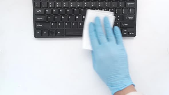 Hand in Blue Rubber Gloves and White Tissue Disinfecting Keyboard