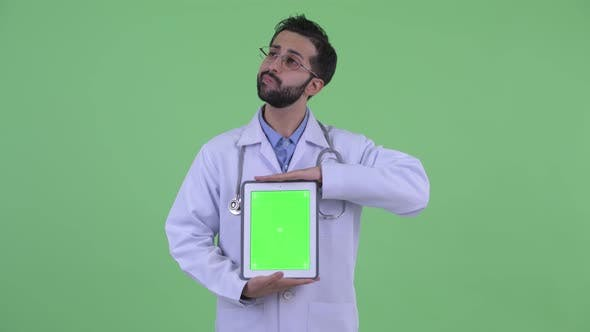 Thumbnail for Happy Young Bearded Persian Man Doctor Thinking While Showing Digital Tablet