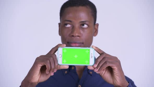 Thumbnail for Face of Young Happy African Businessman Thinking While Showing Phone