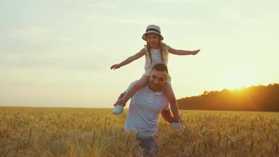 Little Girl Sitting on Shoulders of Father and Having Fun