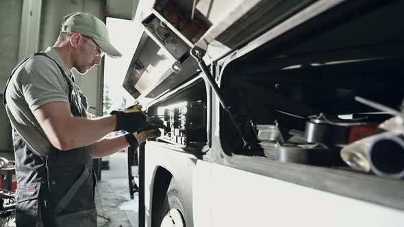 Thumbnail for Auto Mechanic Inspecting Fuses In Coach Bus.