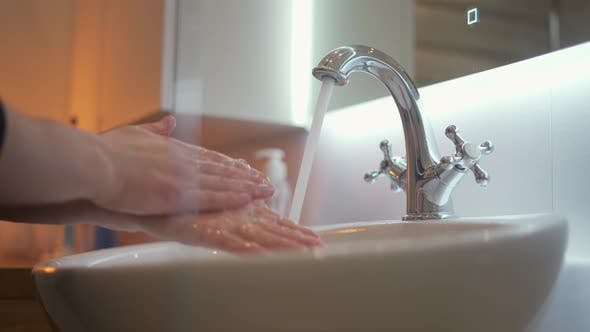 Man Washing Hands with Soap in Bathroom
