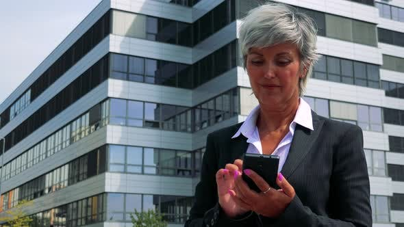 Thumbnail for Business Middle Age Woman Works on the Smartphone - Company Building in the Background