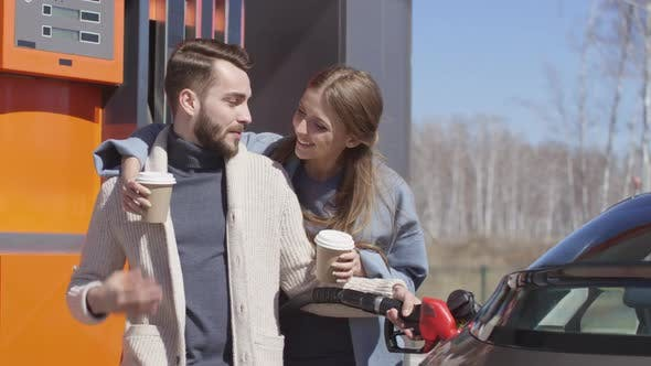Cover Image for Woman Bringing Coffee to Husband at Gas Station