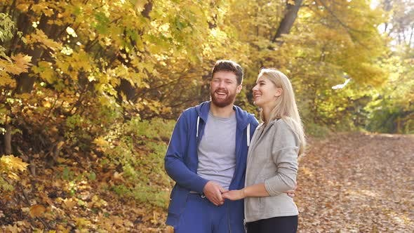 Happy Sports Couple Having Fun in the Forest Standing in Contemplation of Bright Autumn Yellow