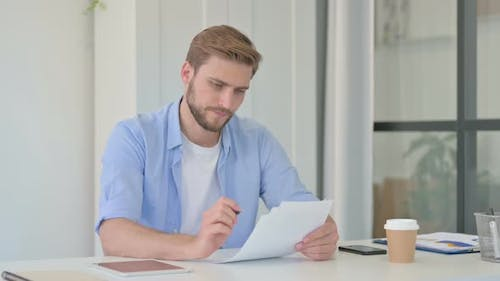 Young Creative Man Reading Documents in Office