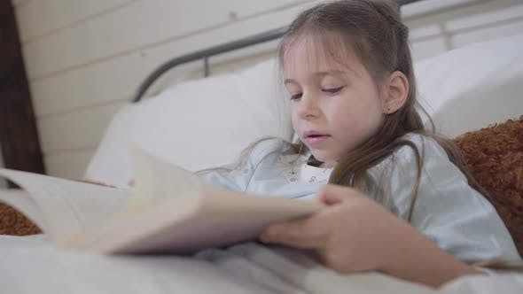 Close-up of Little Brunette Caucasian Girl Reading Book in Bed. Happy Charming Child Enjoying