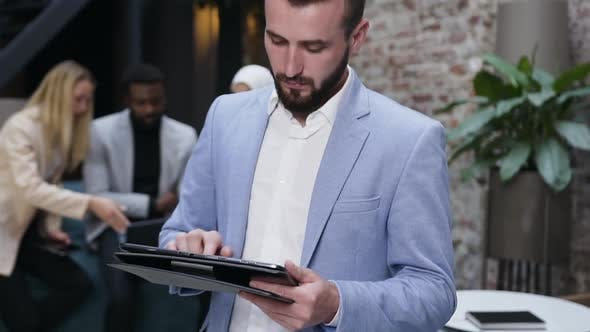 Cover Image for Businessman Making Notes in Tablet Computer App on the Background of His Co Workers